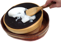 L'engrut fred essent tamisat en el norikoshi. A sota, el noribon per recollir l'engrut ja tamisat.