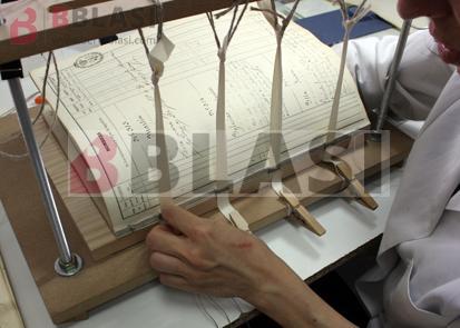 Procés de restauració: cosit del bloc del llibre un cop consolidats els quadernets
