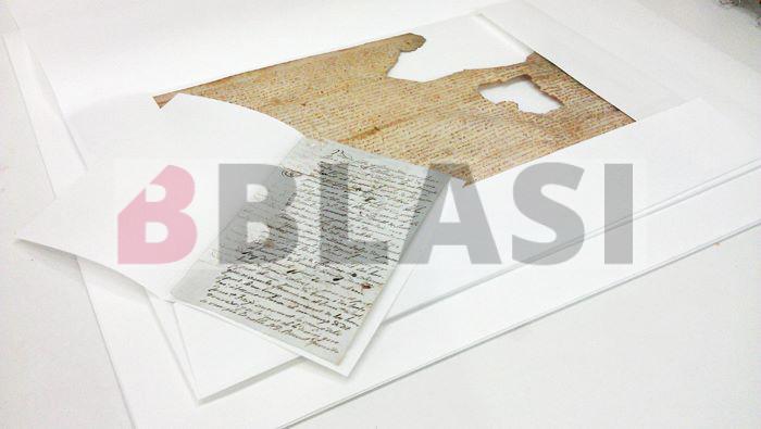 Un document de pergamí i un document de paper protegits amb camises de paper de conservació de pH neutre