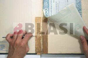 Reparació d'un llibre realitzada amb cinta de precinte totalment envellida